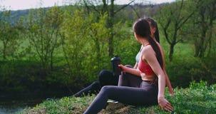 Duas senhoras atrativas que apreciam o tempo junto depois que um exercício duro os exercita na natureza em um lugar bonito video estoque