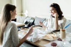 Duas senhoras bonitas que comem em um restaurante ao ter um conve Foto de Stock Royalty Free