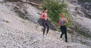 Duas senhoras com um corpo apto após um dia duro do exercício através da água potável sedento da estrada da montanha de um plásti vídeos de arquivo
