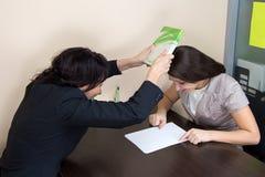 Duas senhoras do negócio que sentam-se no escritório e que argueing Imagens de Stock