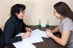 Duas senhoras felizes do negócio que sentam-se no escritório Imagem de Stock