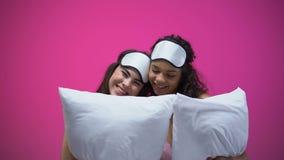 Duas senhoras nos pijamas e nas máscaras de olho que guardam descansos, abraçando e rindo, resto video estoque