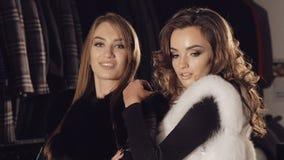 Duas senhoras que levantam em casacos de pele ricos no boutique para anunciar lentamente filme