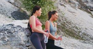 Duas senhoras sedentos após um exercício duro na natureza pararam ao lado do pedras e a água potável grandes do plástico vídeos de arquivo