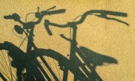 Duas sombras das bicicletas que caem na parede amarela Volante, sela e rodas visíveis imagem de stock