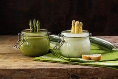 Duas sopas de creme do aspargo brancas e verdes nos frascos de vidro em um rus Foto de Stock Royalty Free