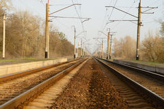 Duas trilhas de estrada de ferro com plataformas para passageiros de aterrissagem Foto de Stock