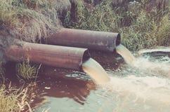 Duas tubula??es de esgoto derramam para fora ao rio/desperdi?am o volume de ?gua da tubula??o de ?gua no lago toned imagem de stock