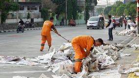 Duas vassouras que limpam a rua dos desperdícios Fotografia de Stock Royalty Free