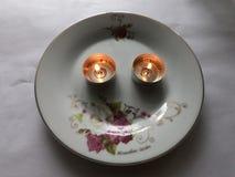 Duas velas de queimadura em uma placa imagem de stock