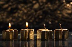 Duas velas douradas do advento iluminadas com fundo do bokeh Foto de Stock