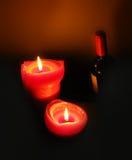 Duas velas iluminadas e uma garrafa do vinho tinto Fotografia de Stock