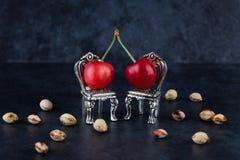 Duas vermelho - cerejas maduras deliciosas em cadeiras de prata pequenas com che Foto de Stock Royalty Free