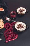 Duas xícaras de café, cappuccino perto dos corações vermelhos no fundo preto da tabela Dia do Valentim Amor Pequeno almoço românt Imagens de Stock