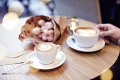 Duas xícaras de café com coração e flores na tabela de madeira no café Mão do homem que guarda um copo Bokeh no fundo Foco no cu  Imagens de Stock Royalty Free