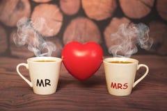 Duas xícaras de café com um coração dão forma em um fundo de madeira fotos de stock royalty free