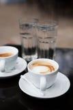 Duas xícaras de café e águas Fotografia de Stock