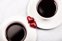 Duas xícaras de café e doces dados forma coração Imagem de Stock