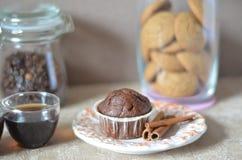Duas xícaras de café na tabela Uma tabela com a placa do café da manhã com queque, em um fundo de um frasco de feijões de café Imagem de Stock