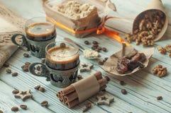 Duas xícaras de café no vintage metal copos, uma caixa do halwa, datas, feijões de café, porcas e canela Imagem de Stock