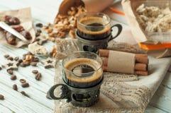 Duas xícaras de café no vintage metal copos, uma caixa do halwa, datas, feijões de café, porcas e canela Fotografia de Stock Royalty Free