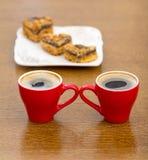 Duas xícaras de café vermelhas e uma placa com bolos Imagens de Stock Royalty Free
