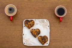 Duas xícaras de café vermelhas e uma placa do quadrado branco com bolos Fotos de Stock