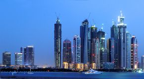 Dubai. Scenic view of illuminated skyline of Dubai city at night with boat in foreground, United Arab Emirates