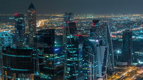 Dubai business bay towers illuminated at night timelapse. Rooftop view of some skyscrapers and new towers under stock footage