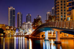 Dubai cityscape at dawn. Scenic view of illuminated skyline of Dubai cityscape at dawn with bridge over river or sea in foreground, United Arab Emirates Stock Photo