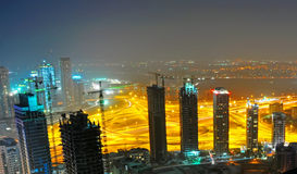 Dubai Construction Site at Night. A night time view of a construction site with a traffic junction lit up by night lights Royalty Free Stock Photos