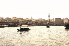 Dubai Creek with abra boats. Local people and tourists using water taxi and ferry in old town river. Traditional cruise. Scenic Arabian city view with mosque royalty free stock images