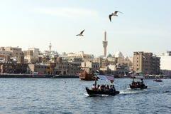Dubai Creek - abra, fartyg, minaret Arkivfoton
