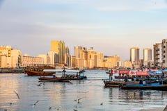 Dubai Creek con las porciones de gaviotas y de barcos en la puesta del sol, United Arab Emirates del abra fotos de archivo libres de regalías