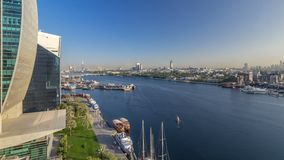 Dubai creek landscape timelapse with boats and ship in port and modern buildings in the background during sunset. Dubai creek landscape timelapse with boats and stock video footage