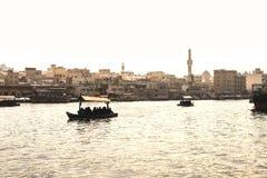 Dubai Creek mit abra Booten Lokale Leute und Touristen, die Wassertaxi und -fähre im alten Stadtfluß verwenden Traditionelle Kreu lizenzfreie stockbilder