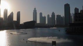 Dubai dancing fountains at sunset. Dubai fountain near Burj Khalifa illuminated by the city at sunset stock footage