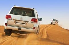 DUBAI - 2 DE JUNIO: Conduciendo en los jeeps en el desierto, entretenimiento tradicional para los turistas Foto de archivo libre de regalías