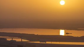 Dubai downtown with sunrise timelapse. Top view from above. Dubai downtown with sunrise timelapse with traffic on the road and reflection in water of creek at stock footage