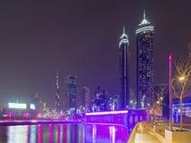 Dubai - el horizonte nocturno sobre el canal y en el centro de la ciudad con la cascada en el puente Fotografía de archivo libre de regalías