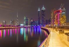 Dubai - el horizonte nocturno sobre el canal y en el centro de la ciudad con la cascada en el puente Imágenes de archivo libres de regalías
