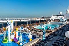 Dubai, Emiratos Árabes Unidos - 12 de dezembro de 2018: andar superior do navio de cruzeiros com piscina e os passageiros de desc imagens de stock royalty free