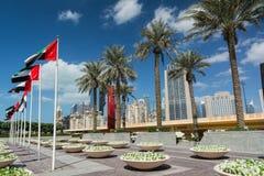 DUBAI, EMIRATOS ÁRABES UNIDOS - 10 DE DEZEMBRO DE 2016: Rua de Dubai perto da alameda de Dubai com palmeiras e prédios modernos Fotografia de Stock Royalty Free