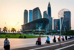 Dubai, Emiratos Árabes Unidos - 18 de maio de 2018: Povos que apreciam o por do sol com construção da ópera de Dubai e os arranha imagens de stock