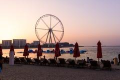Dubai, Emiratos Árabes Unidos - 8 de março de 2018: Sunbeds e o por do sol romântico em JBR, praia da estância de verão de Jumeir imagem de stock