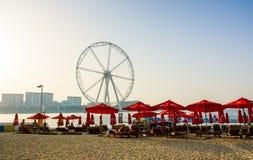 Dubai, Emiratos Árabes Unidos - 8 de março de 2018: Sunbeds em JBR, praia da estância de verão de Jumeira com Ain Dubai, atração  fotos de stock royalty free