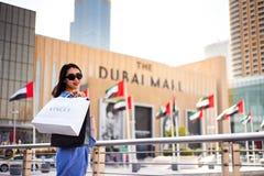 Dubai, Emiratos Árabes Unidos - 26 de março de 2018: Turista asiático na frente da entrada principal da alameda de Dubai imagem de stock royalty free