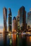 Dubai, Emiratos ?rabes Unidos - 14 de fevereiro de 2019: Arranha-c?us modernos do porto de Dubai e iate luxuosos na hora azul imagens de stock royalty free