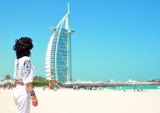 DUBAI FÖRENADE ARABEMIRATEN - MAJ 2017: Kvinna framme av Burj Al Arab, berömda gränsmärken av Förenade Arabemiraten som ses från  Royaltyfri Fotografi