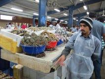 Dubai-Fischmarkt Auf dem Zähler in den Beckenmarinereptilien Verkäufer hasten herum lizenzfreie stockfotografie